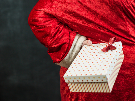 sneaking: Santa sneaking in with a gift hidden behind his back. Stock Photo