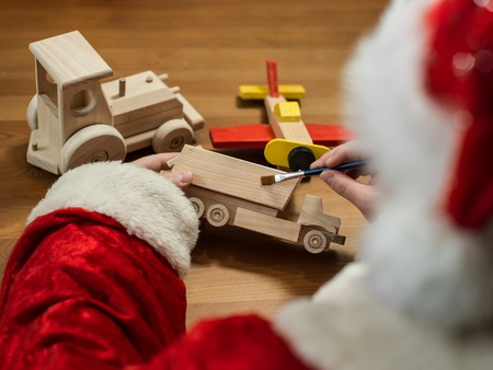 Santa Claus sitting in his workshop painting a toy airplane. Horizontal composition.