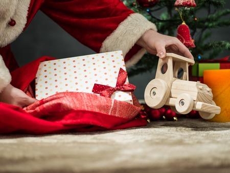 saint nicolas: holidays, celebration and people concept - close up of santa claus putting present under christmas tree