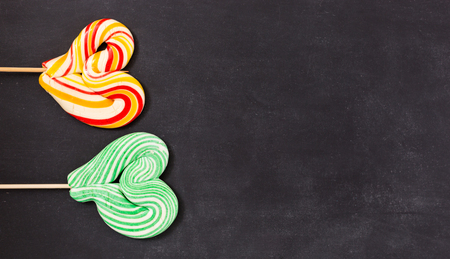 obesidad infantil: shaped lollipop on black chalkboard background. Valentines day concept.