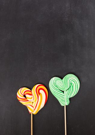 obesidad infantil: shaped lollipop on black chalkboard background. Valentines day concept.