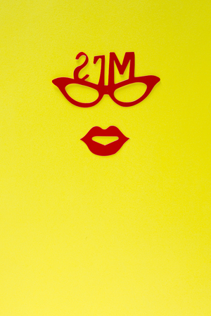 solid color: woman paper cutout face with glasses and heart on solid color