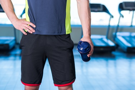 Closeup of man in gym with blue shaker