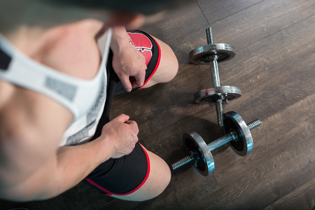 powerfully: Top view of man in a gym on wooden background with weights