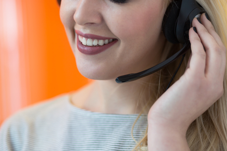 hands free: Smiling young business woman wearing a headset answering calls at a client service centre or wanting to communicate hands free while continuing to work in her office