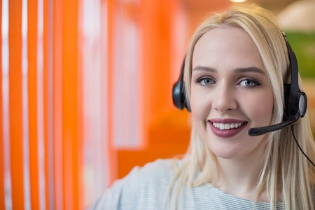 part of me: Portrait of support phone operator in headset at workplace. To provide maximum quality, I have made this image by combination of two photos. You can use left part for slogan, big text or banner.