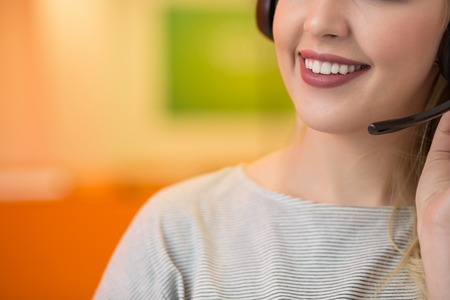 Close up of a blonde smiling woman wearing headset in her office