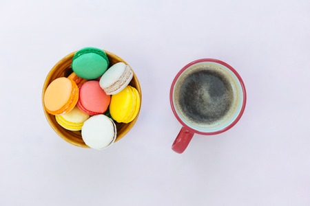 Coffe cup and colorful macaroons on pastel background, top view Stock Photo