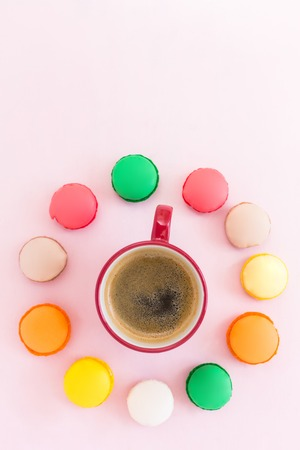 fattening: Coffe cup and colorful macaroons on pastel background, top view Stock Photo