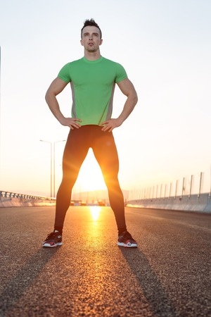 male athlete: Stretching after jogging. sunset shot on highway