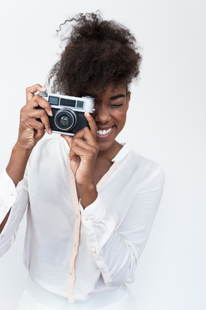 Afro american woman taking a picture with a  vintage camera Stock Photo