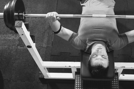 Young Man In Gym Exercising Chest On The Bench Press - top view
