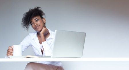 Pretty afro american businesswoman working at desk in her office