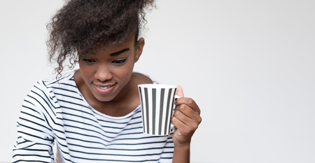 afro american woman with striped t-shirt and striped cup of caffee or tea