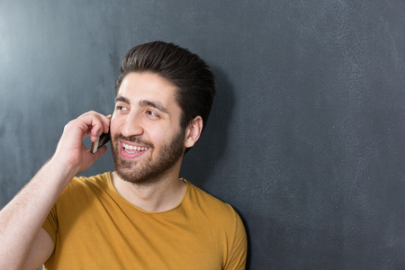 Portrait of young businessman standing at office against wall and making call while smiling and looking away.