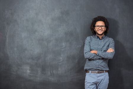 pensive young African American man standing against a blank chalkboard, with copyspace
