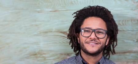 Studio portrait of cool black young man with black glasses, striped retro 70s shirt and retro afro hair on rustic background