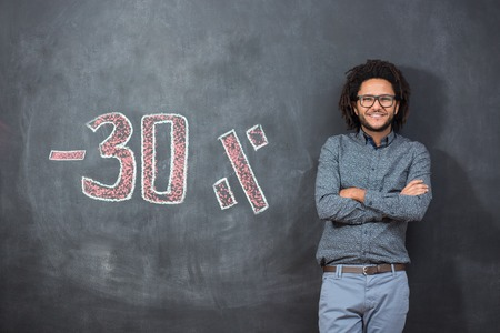 mixed race afro man standing in front of chalkboard with discount numbers, discount concept, sale concept