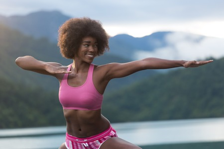 portrait of female athlete stretching outdoors in park Stock Photo