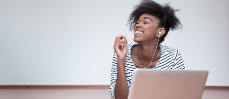 Happy African American woman with a lovely frizzy afro hairdo lying on the wooden floor with a laptop computer smiling at the camera with a blank white wall and copyspace behind her