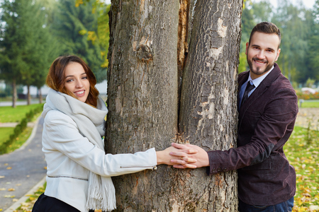 Couple peeking around opposite sides of tree