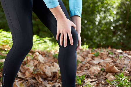 sprain: Knee Injury - sports running knee injuries on woman. Male runner with pain from sprain knee. Close up of legs, muscle and knee outdoors.