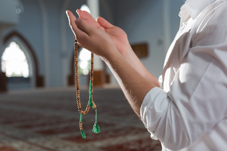 escapism: hand holding a muslim rosary