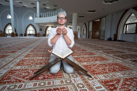 Young muslim man is praying in the mosque