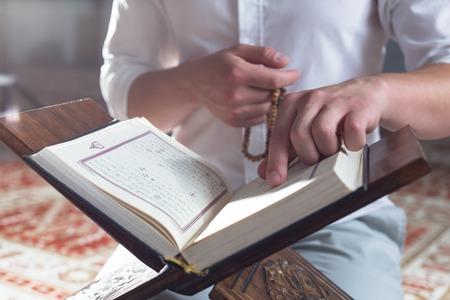 recite: hand holding a muslim rosary