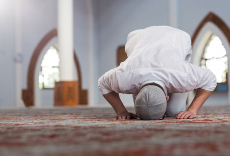 Religious muslim man praying inside the mosque Imagens