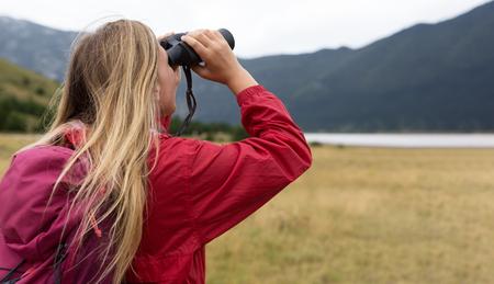 young blonde woman hiking and watching through binoculars.