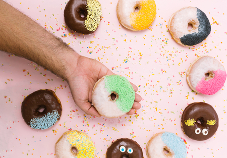 junkfood: people, food, junk-food and eating concept - close up of female hand holding glazed donut