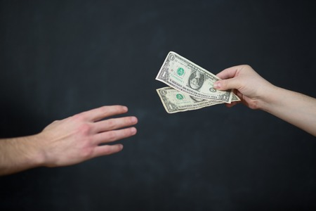 venality: Concept - corruption. Giving a bribe. Money in hand