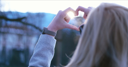 Beautiful caucasian blonde woman  showing heart sign with fingers, valentine day concept  love