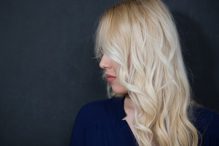 opting: Blond woman in shirt against chalkboard, copyspace Stock Photo