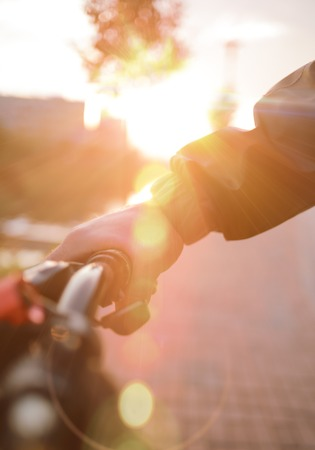 people, travel, tourism, leisure and lifestyle - close up of young hipster man hands holding fixed gear bike wheel on city street - sunset