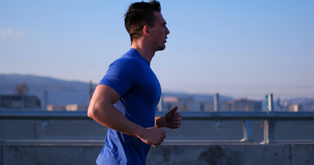 Running at sunrise man exercising for marathon and workout fitness