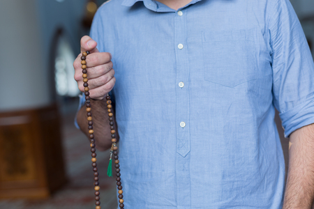 recite: hand holding a muslim rosary