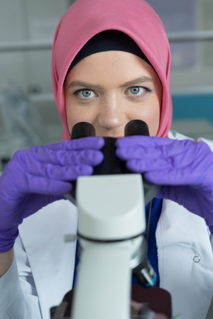 urogenital: muslim lab worker doing an analysis