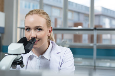Young scientist in white uniform working in laboratory Stock Photo