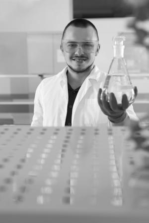 bata de laboratorio: Jóvenes científicos en bata de laboratorio, mientras sonríe a la cámara