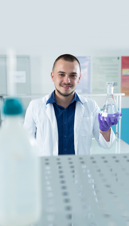 Modern chemist looking at liquid in flask in laboratory Stock Photo