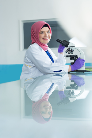 urinalysis: muslim lab worker with hijab or researcher doing an analysis in labaratory Stock Photo