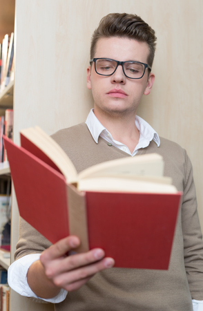 post secondary schools: young male college student reading in the library