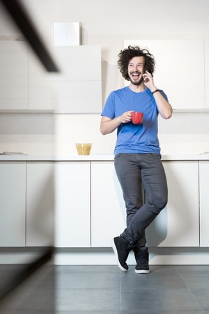 kitchen, men and smart phone. Man in kitchen using cell phone and drinking coffe