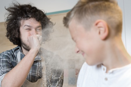 7 year old boys: a father and his son preparing a cake in the kitchen. Father and son having flour fight in kitchen Stock Photo