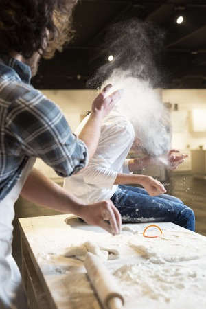 7 year old boys: Flour fight in kitchen. Father and his son preparing a cake in the kitchen