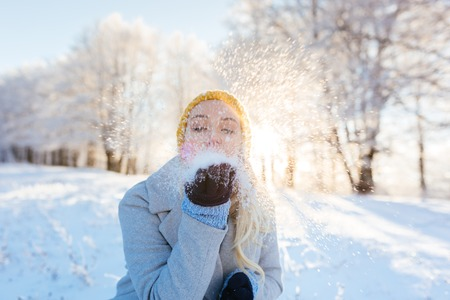 Winter girl blowing snow in frosty winter park, young woman having fun in winter park. Sunset shot with selective focus 스톡 콘텐츠