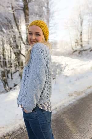 Winter portrait of a young smiling woman in a yellow hat on a background sunset. Winter day