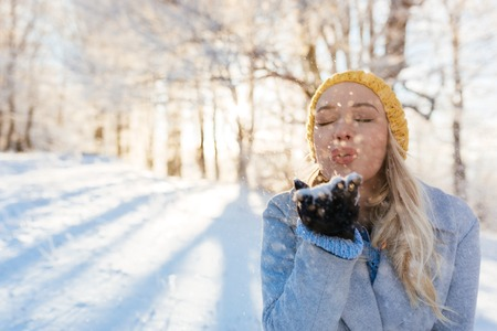 woman blowing: Beautiful young woman blowing snowflakes, selective focus Stock Photo